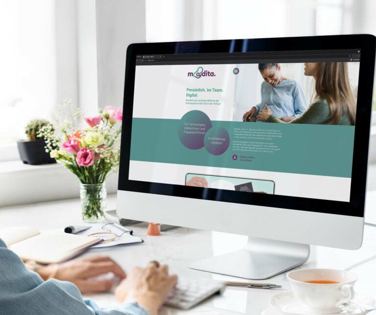 Eine Frau sieht sich am Computer Madita Online an